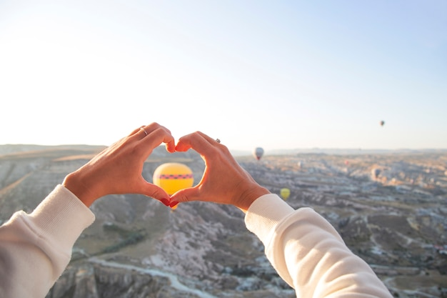 Manos de mujer en forma de corazón con el telón de fondo de globos voladores en el cielo de capadocia vacaciones en turquía viajan durante una pandemia
