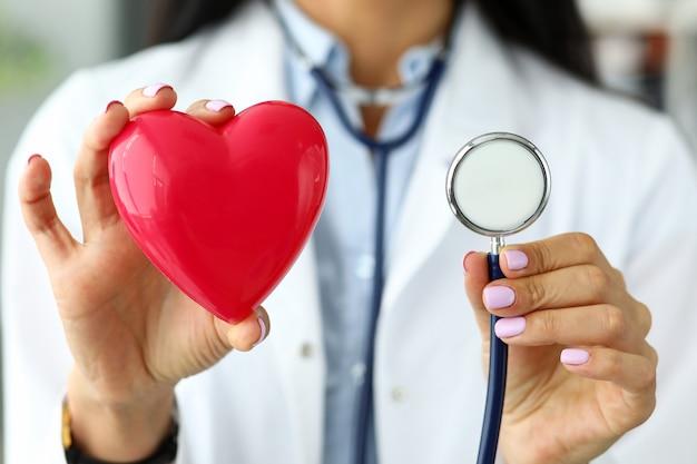 Manos de mujer gp sosteniendo la cabeza del estetoscopio cerca del corazón de juguete rojo