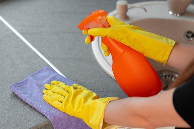 Manos de mujer en guantes amarillos, encimera de limpieza en la cocina