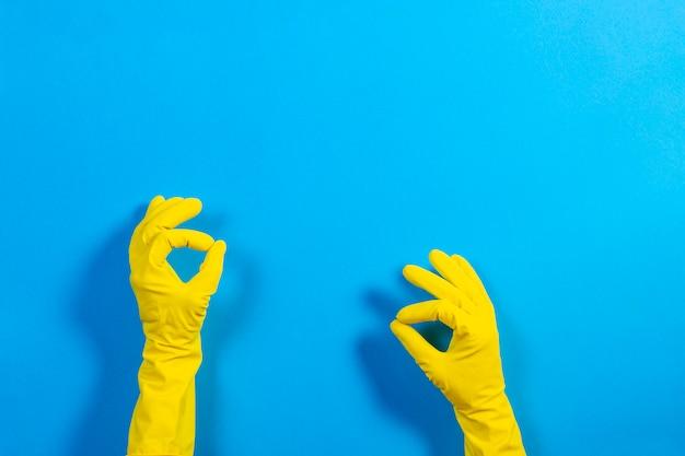 Manos de mujer con guantes de goma amarilla haciendo un gesto que significa sobre fondo azul.