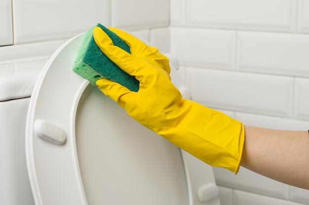 Manos de mujer con guantes de goma protectores amarillos lavan el inodoro