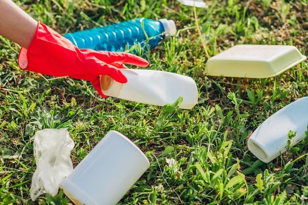 Manos de mujer en guantes de goma roja. mujer recoge basura en la bolsa. voluntario recoger basura en el parque de verano. bonita mujer progresista haciendo un esfuerzo por ayudar al medio ambiente.