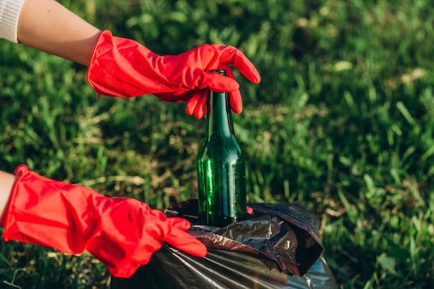 Manos de mujer en guantes de goma roja. mujer recoge basura en la bolsa. voluntario recoger basura en el parque de verano. niña recoge botellas de plástico y vidrio en el paquete