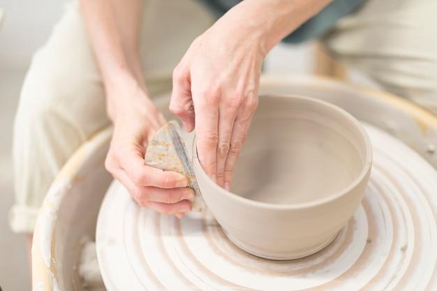Manos de mujer hace olla de barro en la rueda de alfarería