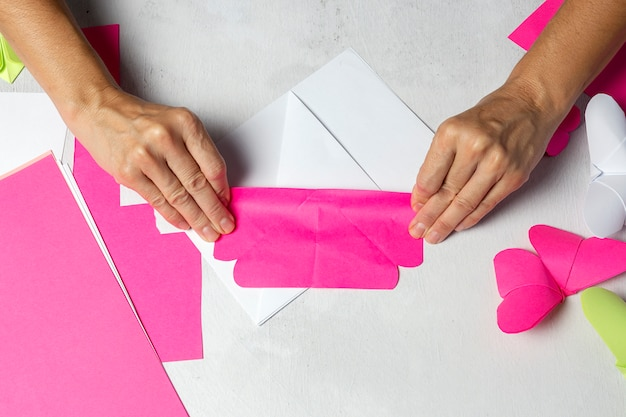 Manos de mujer haciendo animales de origami de papel