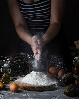 Manos de mujer haciendo pasta estilo rústico oscuro