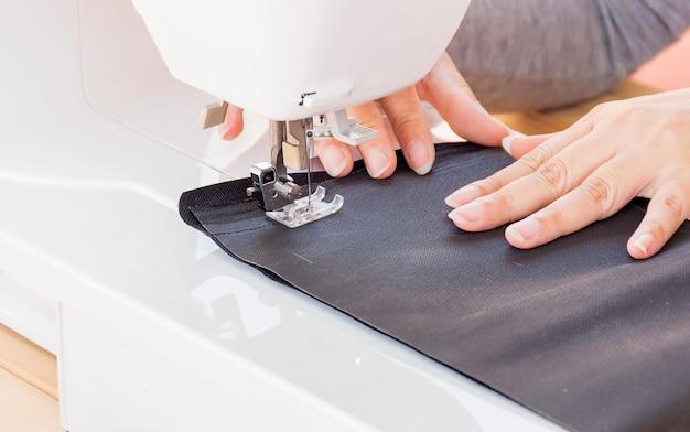 Manos de mujer, haciendo su patchwork usando máquina de coser.