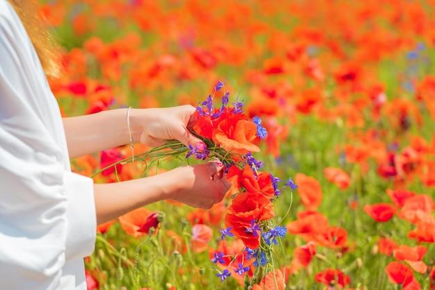Manos de mujer hermosa joven teje una corona de flores de amapola en el campo en verano