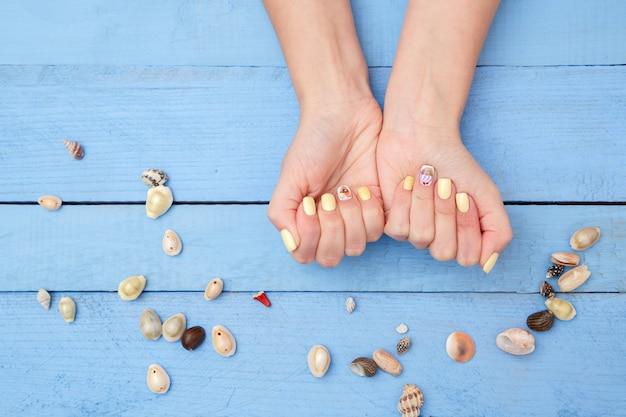 Manos de mujer con una hermosa manicura y conchas