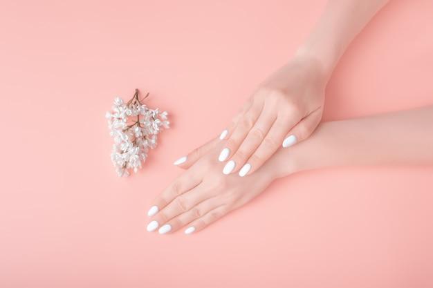 Manos de mujer con hermosa manicura y lila blanca aislado sobre fondo rosa. concepto de cuidado de la piel.