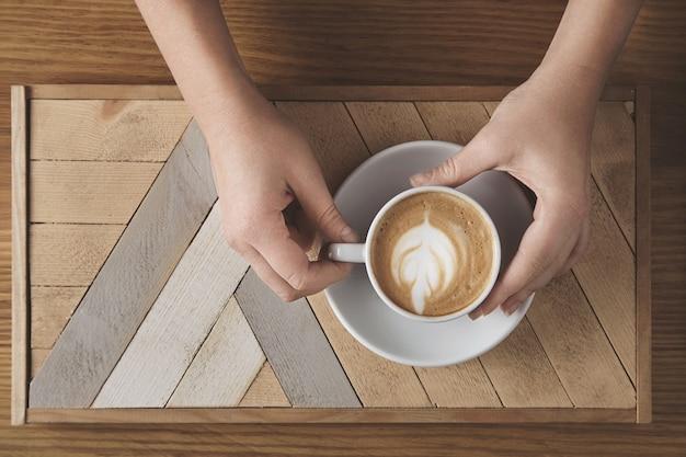 Manos de mujer hermosa sostienen cerámica blanca con capuchino sobre placa de madera y mesa rústica. espuma de leche en la parte superior en forma de árbol. vista superior en la cafetería. concepto de presentación de venta.
