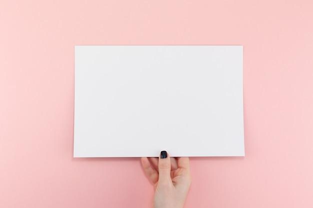 Manos de mujer con hoja de papel a4 en blanco