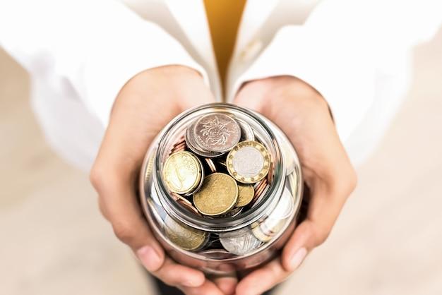 Manos de mujer joven con frasco de vidrio con monedas múltiples dentro