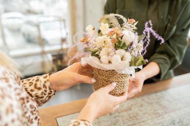Manos de mujer joven tomando una pequeña canasta con ramo de flores mientras visita la floristería para comprar flores para su amiga o madre