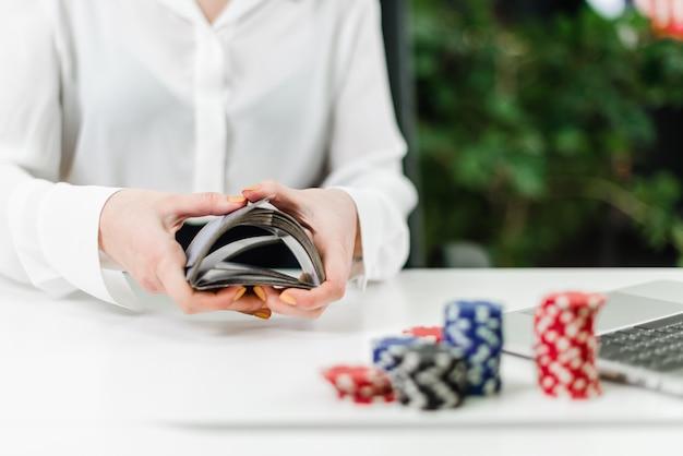 Manos de mujer lanzando cartas mientras juega casino en línea en la oficina