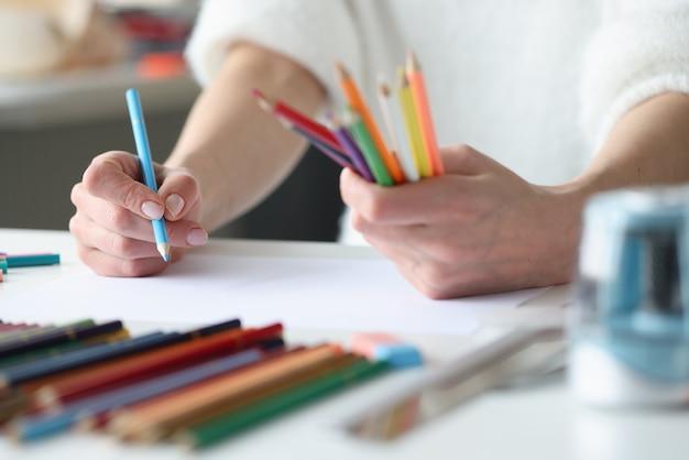 Manos de mujer lápices multicolores para crear bocetos de ropa de moda
