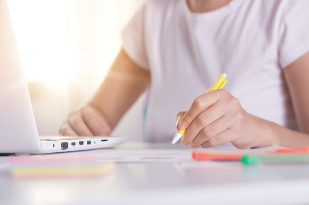 Manos de mujer con lápiz amarillo escribiendo algo en peper, trabajando en línea, mujer trabajando en la computadora portátil