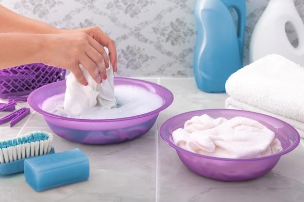Manos mujer lava la ropa a mano en agua jabonosa.