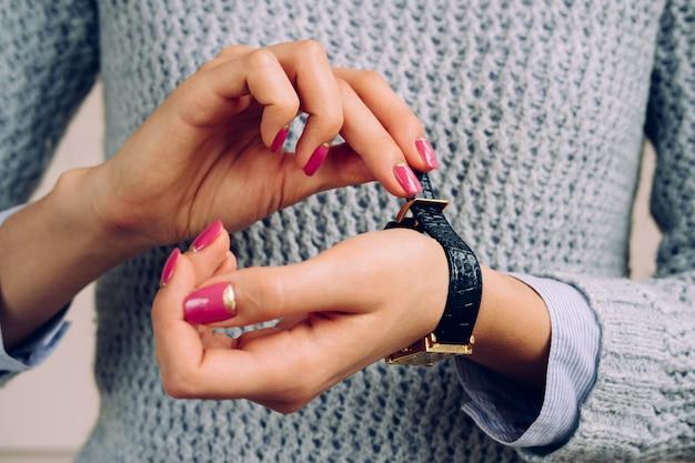 Las manos de mujer con manicura brillante cierran la correa del reloj.