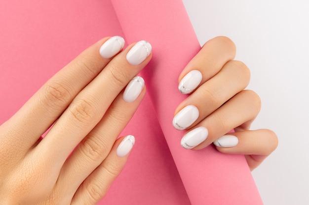 Manos de mujer con manicura francesa blanca de moda