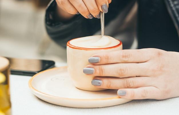 Manos de mujer con manicura sosteniendo una taza con capuccino al aire libre
