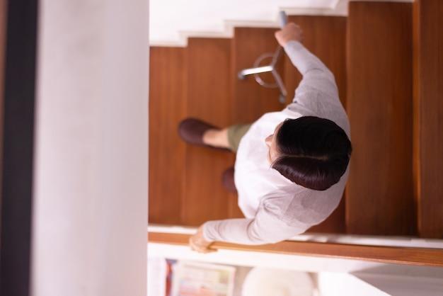 Manos de mujer mayor sosteniendo palos mientras sube escaleras en casa, vista superior