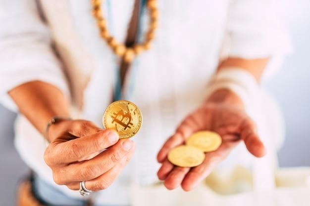 Las manos de la mujer de mediana edad usan y muestran la moneda bitcoin de oro para el nuevo concepto de comercio de comercio de criptomonedas de dinero virtual de tecnología moderna: la vida diaria con nuevos usos e intercambios comerciales