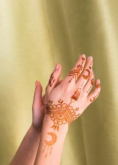 Manos de mujer con mehndi cerca de textil.