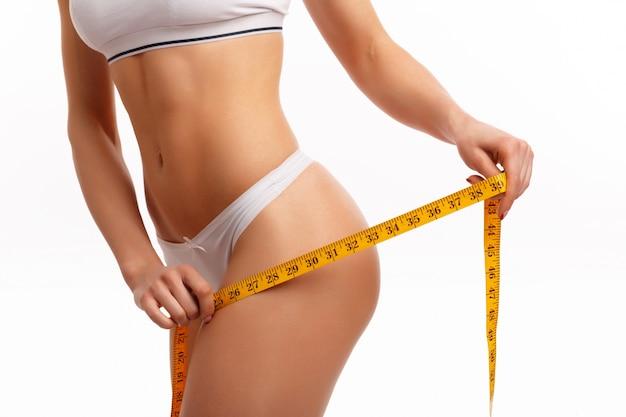 Manos de mujer midiendo el muslo
