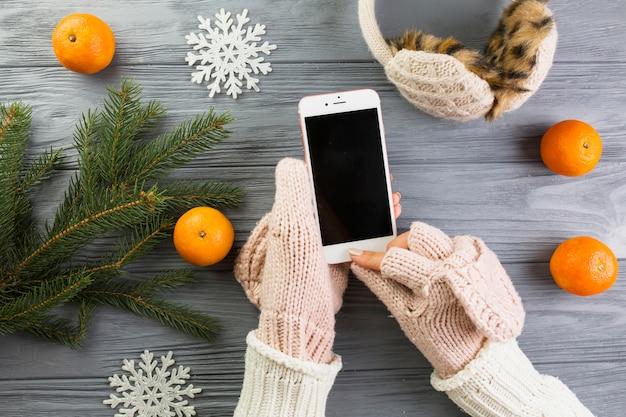 Manos de mujer en mitones con teléfono inteligente cerca de ramas de abeto y copos de nieve de papel