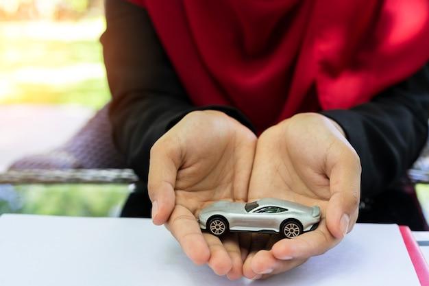Manos de mujer musulmana de negocios sosteniendo el coche