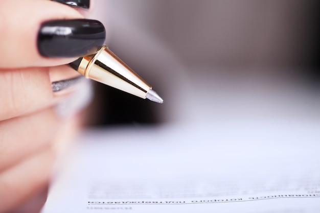 Manos de mujer de negocios firmando el documento del contrato