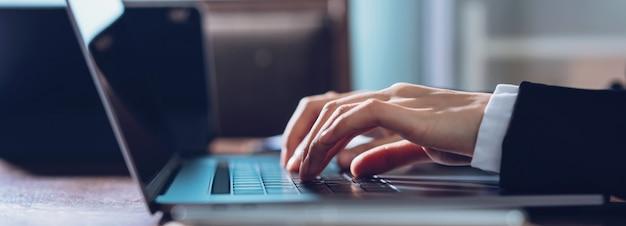 Las manos de la mujer de negocios que mecanografían en el ordenador portátil y que buscan el web, hojeando en el lugar de trabajo en la oficina.
