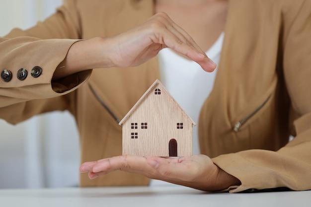 Manos de mujer de negocios sentado y protegiendo la casa modelo en el cuadro blanco.