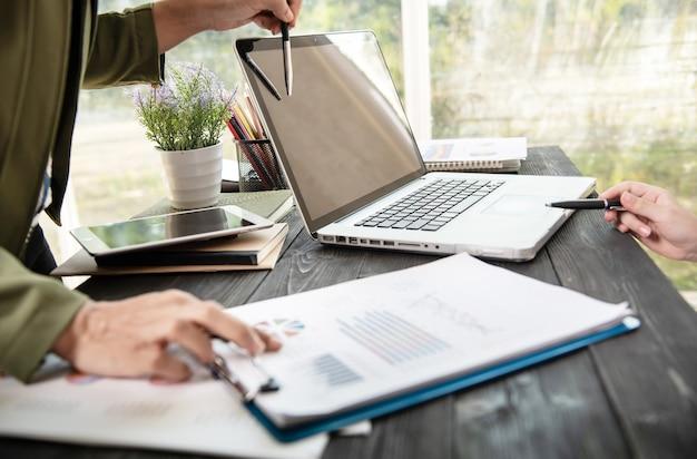 Manos de mujer de negocios usando la computadora portátil colocada en el escritorio de oficina desordenado.