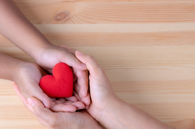 Manos de mujer y niño con corazón rojo para el día mundial del corazón o el día mundial de la salud