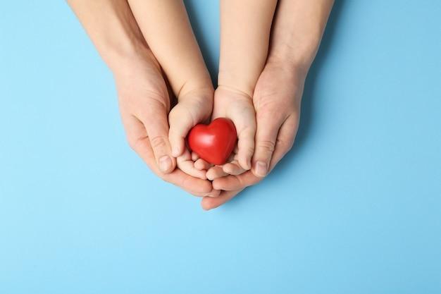 Manos de mujer y niño con corazón rojo en la superficie de color. concepto de cardiología