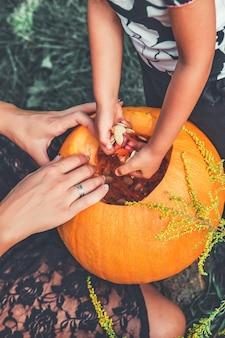 Las manos de la mujer y el niño sacan semillas de una calabaza.