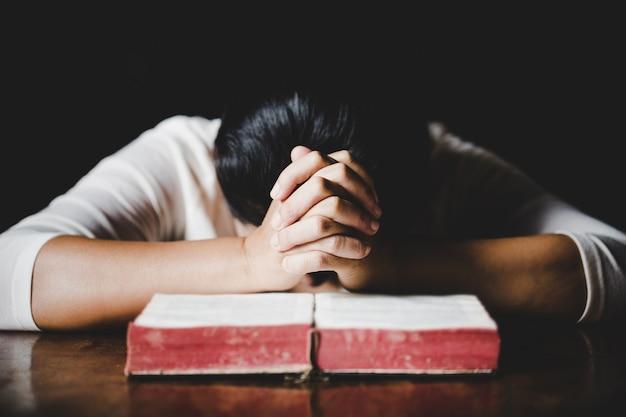 Manos de mujer orando con una biblia en una mesa de madera oscura sobre