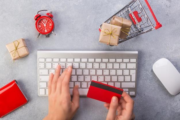 Manos de mujer ordenando regalos en línea, pagando con tarjeta de crédito