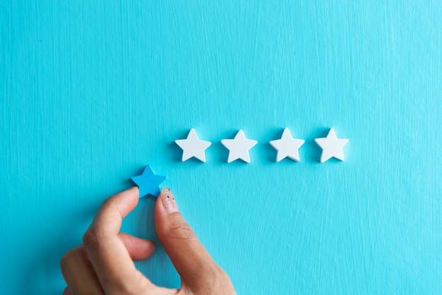 Manos de mujer otorgan calificación de cuatro estrellas a la satisfacción del cliente