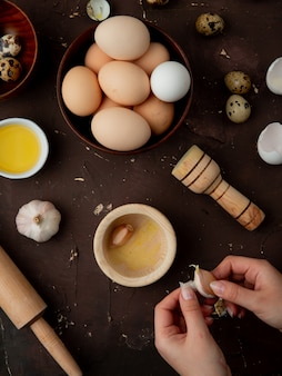 Manos de mujer pelar diente de ajo con mantequilla huevos trituradora de ajo en mesa marrón