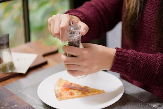 Manos de mujer con pimienta negra y salero en las rebanadas de pizza.