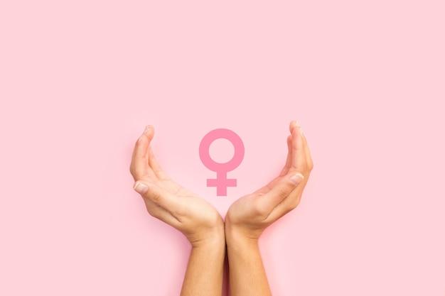 Manos de mujer protegiendo signo femenino sobre un fondo rosa