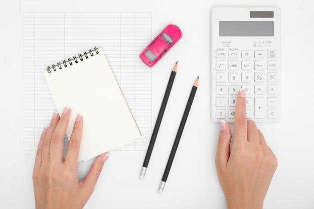 Manos de mujer que calculan los costos de los pagos de los gastos del automóvil con billetes, lápiz, calculadora, tabla de pagos y dinero en dólares