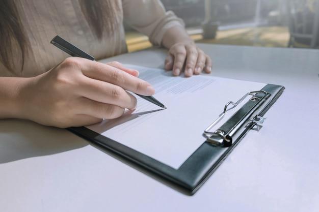 Manos de mujer que completa el formulario de solicitud