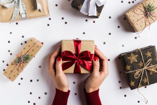 Manos de la mujer que llevan a cabo el arco rojo de la caja de regalo de día de fiesta de la navidad en la tabla festiva adornada