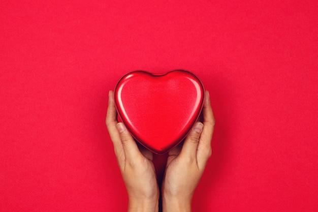 Las manos de la mujer que llevan a cabo el corazón rojo en un fondo rojo. enamorado.
