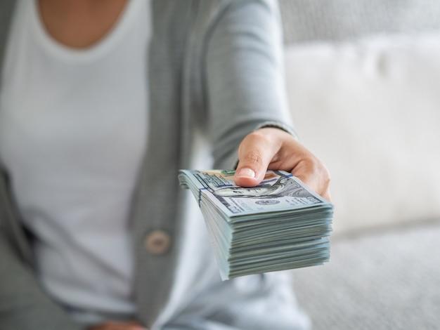 Manos de mujer que nos proponen dinero con billetes de dólar.