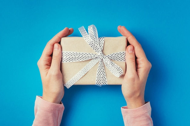 Las manos de la mujer que sostienen la caja de regalo en el fondo azul, visión superior